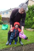 Grandad and toddler sowing Flower Magic seed