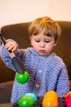 toddler picking up balls with OXO Good Grips tongs